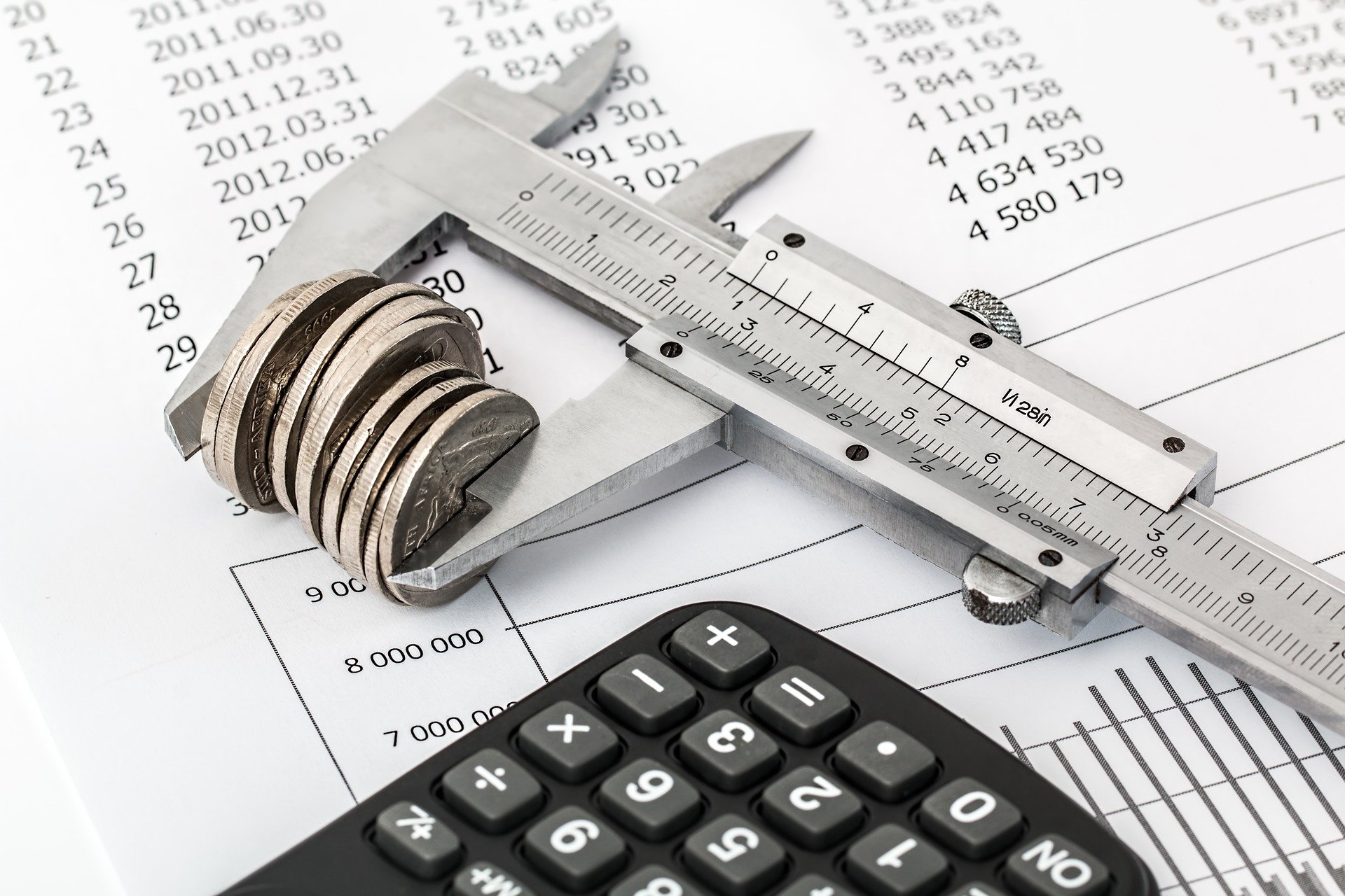 Measuring tool with coins, numbered document and a calculator