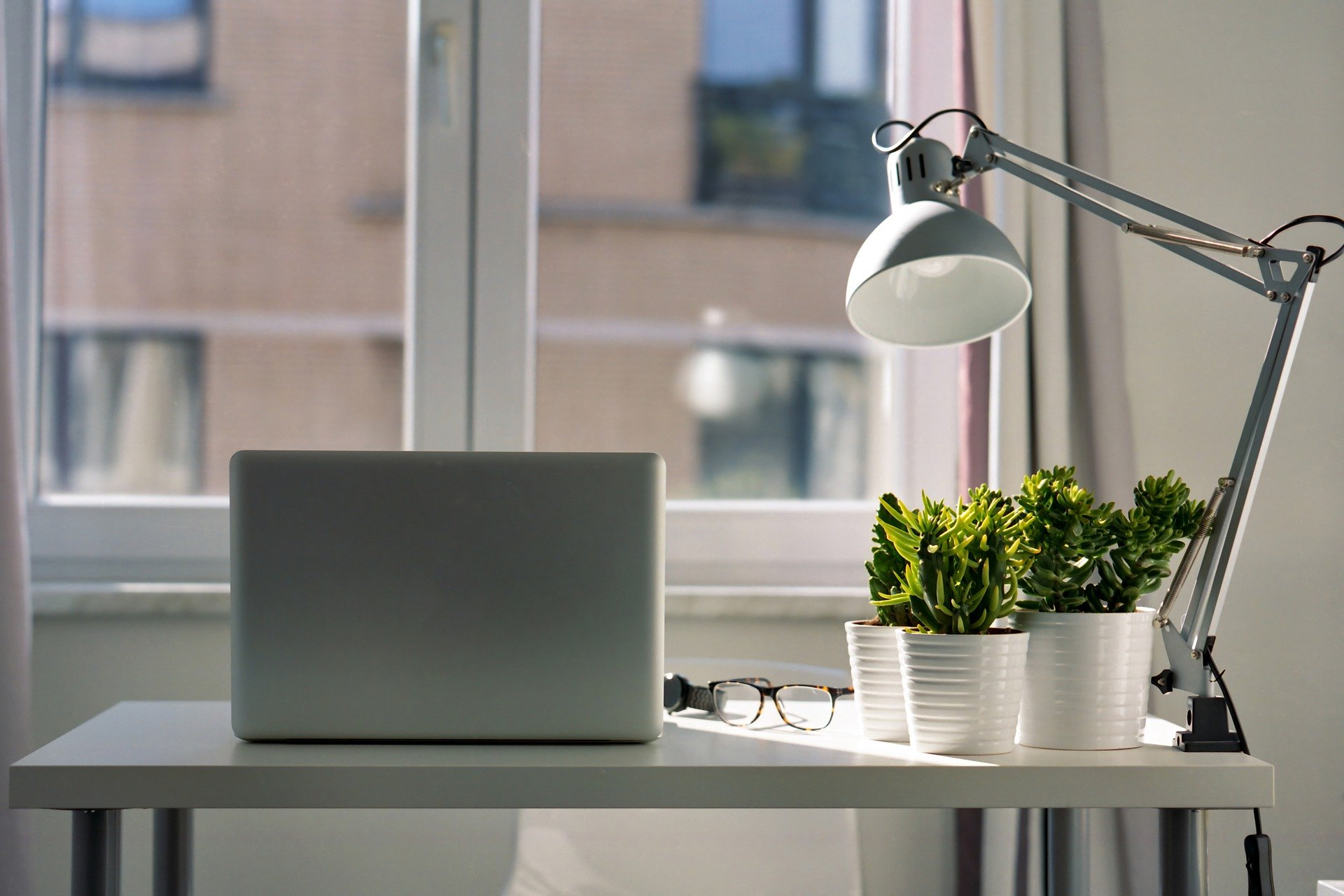 Home office with laptop in front of a window