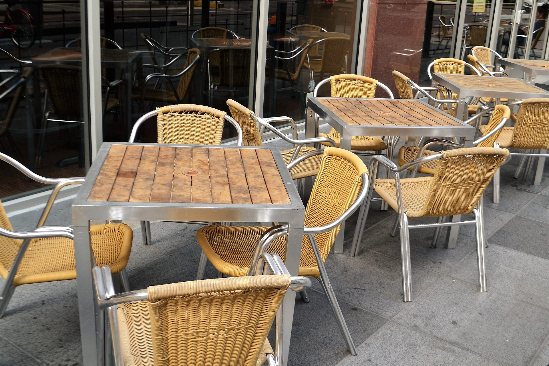 Empty restaurant tables and chairs on a sidewalk
