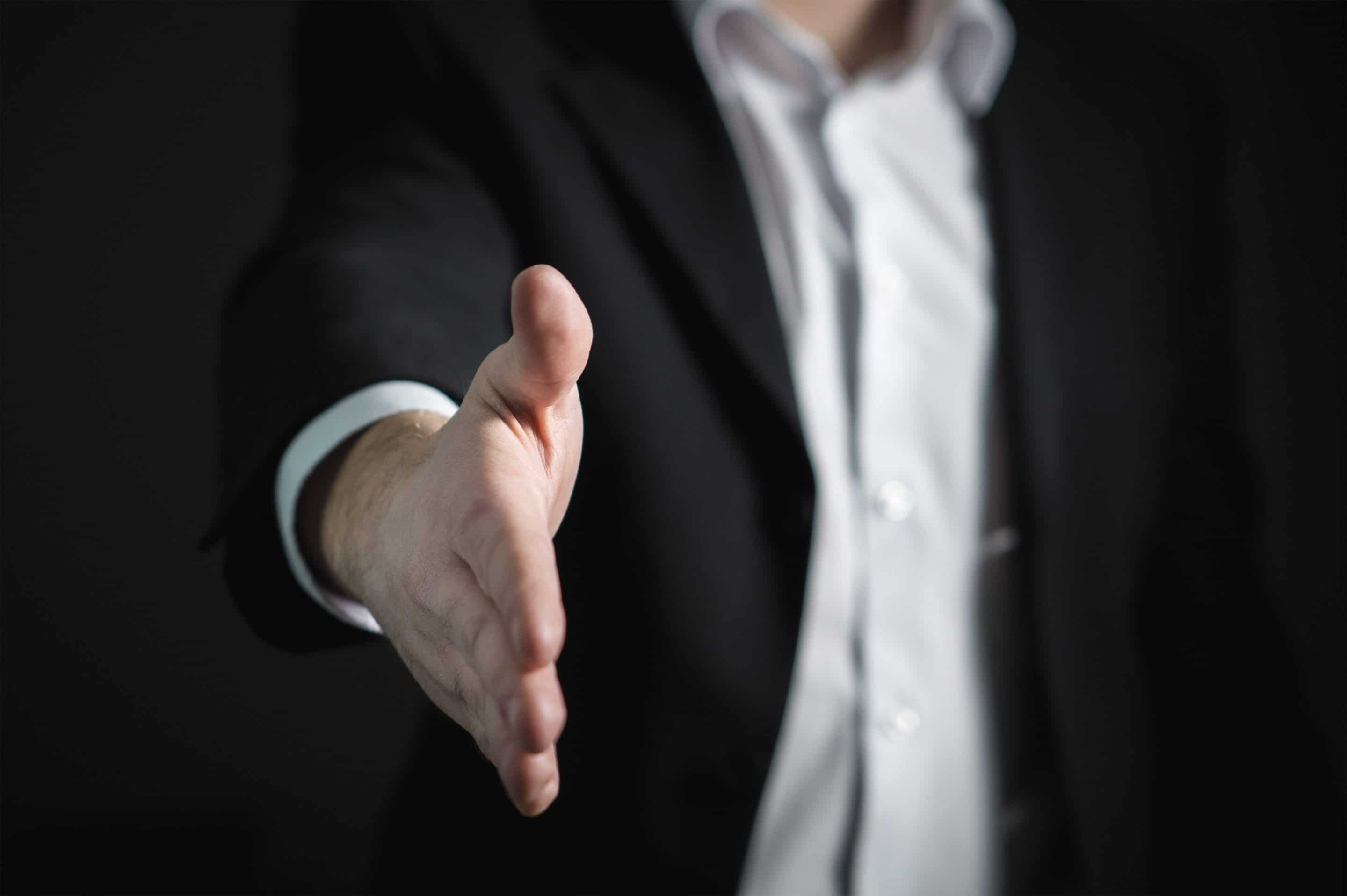 Man in suit with outreached hand for a handshake
