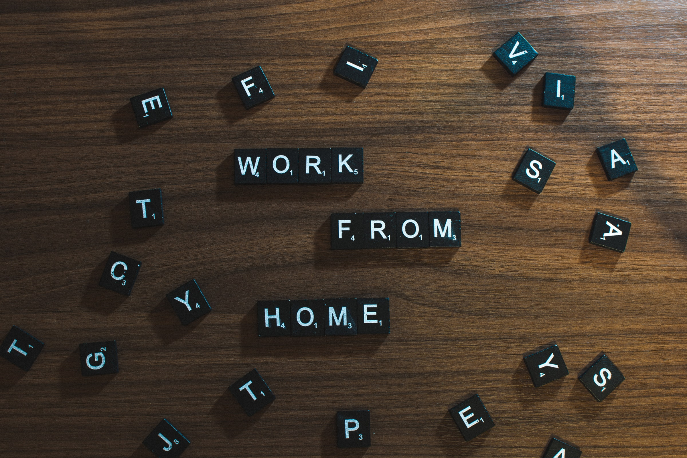 "Letter tiles on a table forming the words ""work from home"""